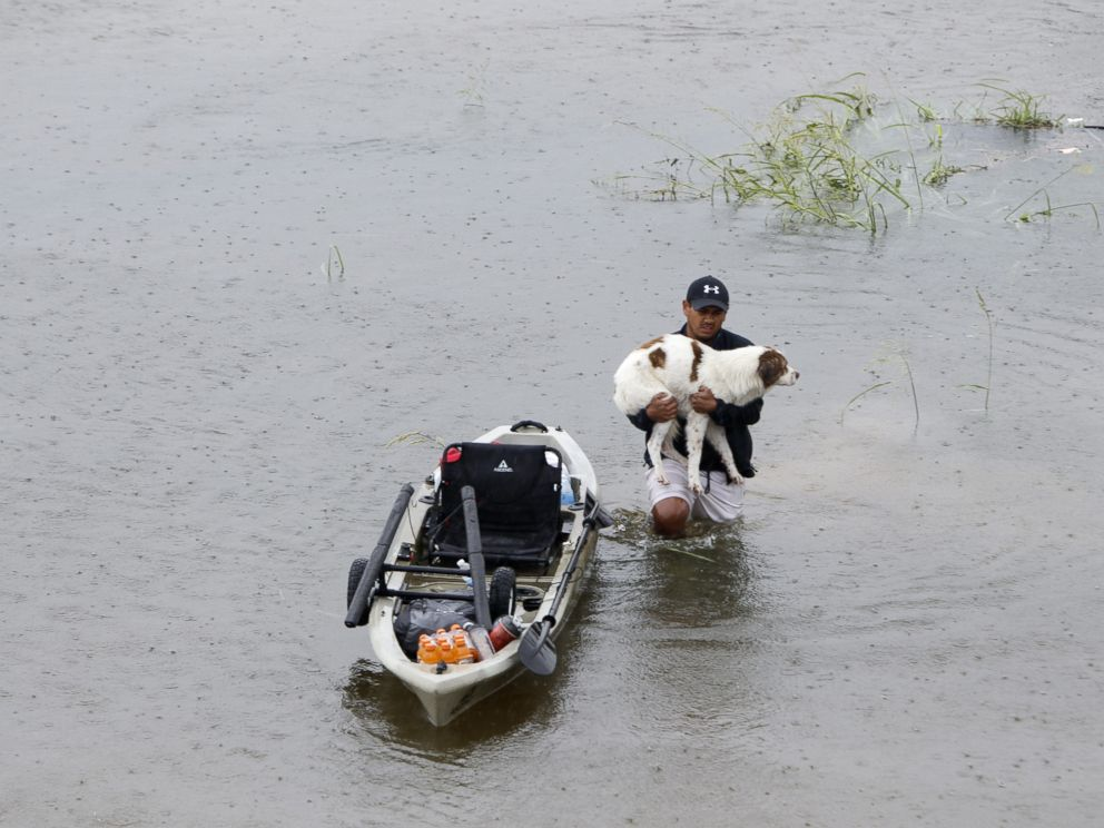 PHOTO: A man holding his dog walks in water in greater Houston area of Texas, Aug. 27, 2017.