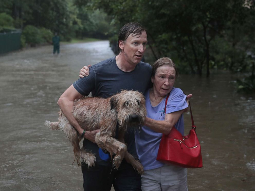 PHOTO: Naomi Coto carries Simba on her shoulders as they evacuate their home after the area was inundated with flooding from Hurricane Harvey, Aug. 27, 2017, in Houston.