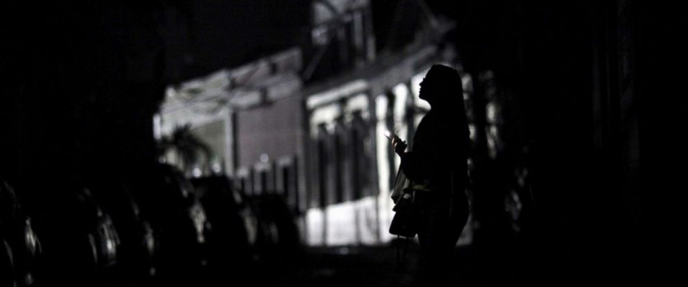 PHOTO: A woman holds a flashlight while standing on a street in the dark, after Hurricane Maria hit the island and damaged the power grid in September, in Old San Juan, Puerto Rico, Oct. 26, 2017.