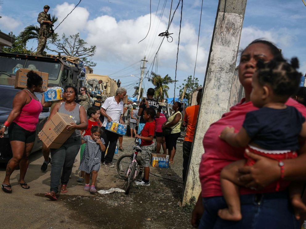 PHOTO: Residents gather to receive food and water from FEMA in a neighborhood without grid electricity or running water on Oct. 17, 2017 in San Isidro, Puerto Rico.