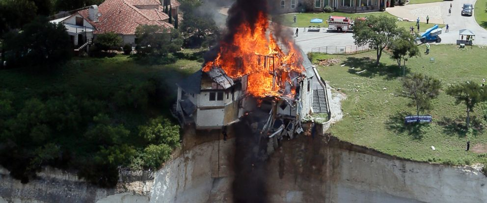 PHOTO: Smoke rises from a house deliberately set on fire, days after part of the ground it was resting on collapsed into Lake Whitney, Texas, June 13, 2014.