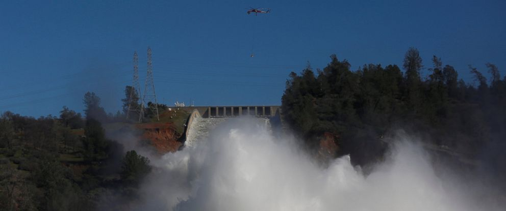 PHOTO: Helicopters carry rocks as water is released from the Lake Oroville Dam after an evacuation was ordered for communities downstream from the dam in Oroville, Calif., Feb. 14, 2017.