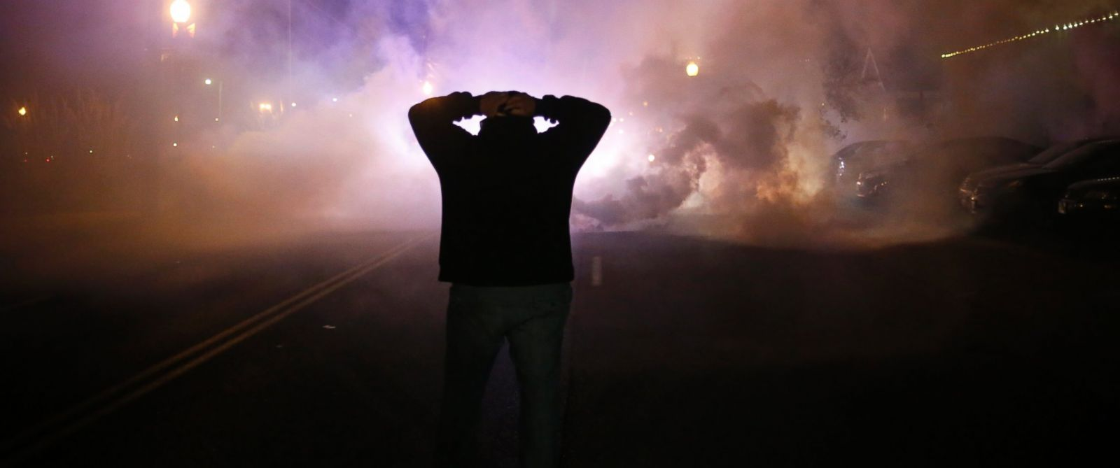 PHOTO: A protester stands with his hands on his head as a cloud of what is reportedly tear gas approaches after a grand jury returned no indictment in the shooting of Michael Brown in Ferguson, Mo. on Nov. 24, 2014.