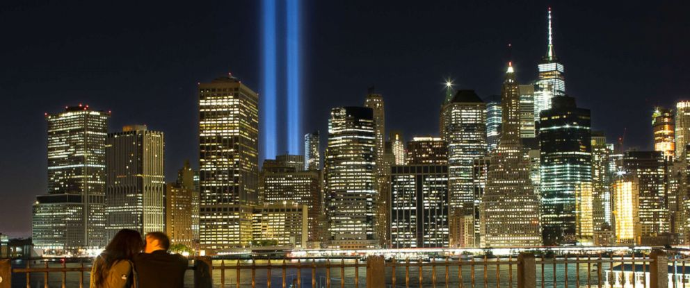 photo a couple embraces on the brooklyn promenade as the tribute in light rises above
