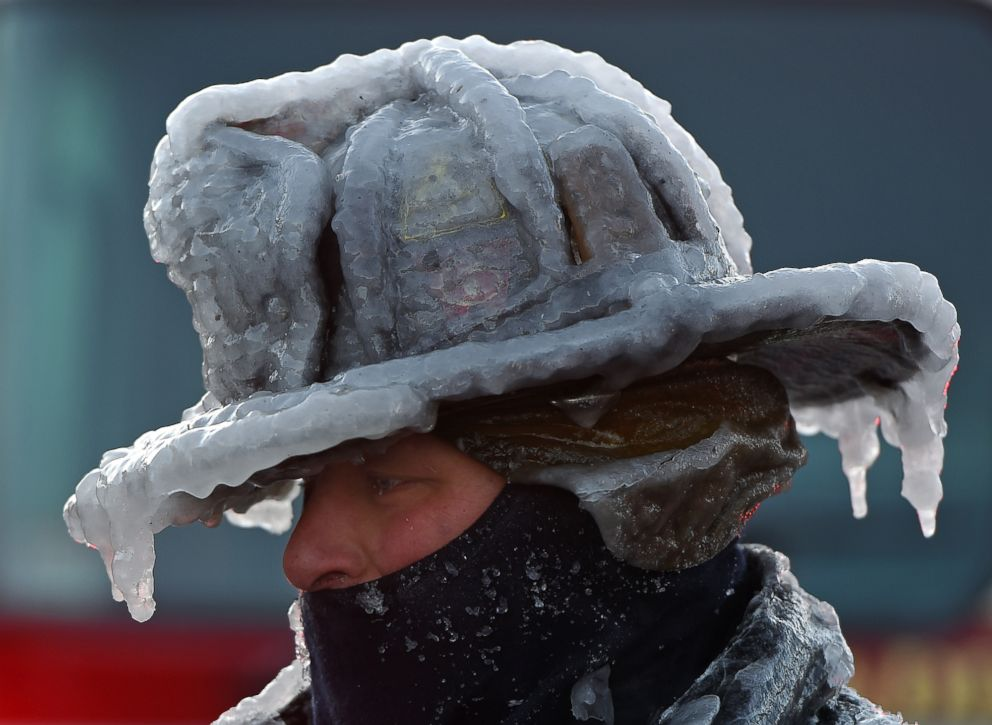 PHOTO: Firefighter Bobby Lehman, with his helmet and bunker gear caked in ice, tries to thaw out after battling a stubborn, wind-driven fire at 238 Wilson Road, Jan. 1, 2018, Nahant, Mass.