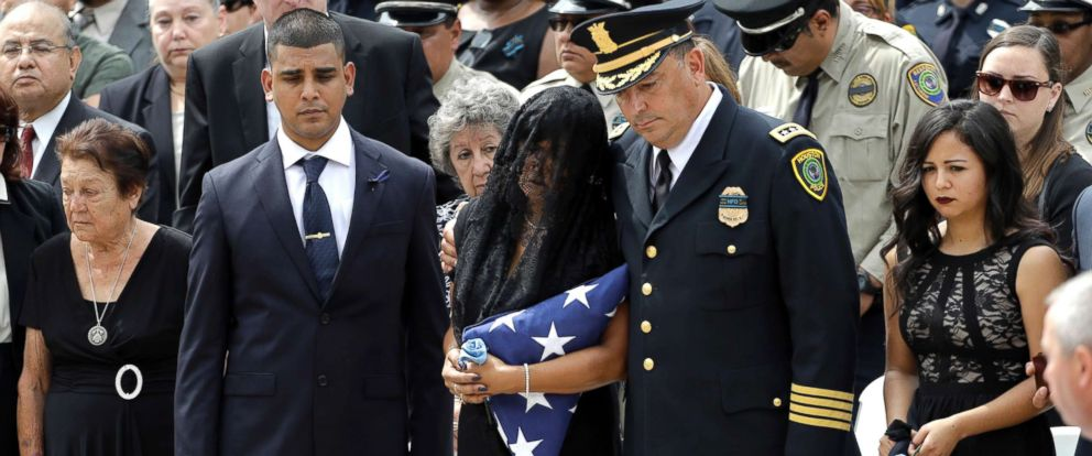 PHOTO: Cheryl Perez, center, is hugged by Houston Police Chief Art Acevedo, while standing with her children Maverick, left, and Sabrina, right, during a funeral service for her husband, Houston Police Sergeant Steve Perez, Sept. 13, 2017, in Houston.