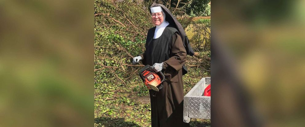 PHOTO: Sister Margaret Ann of Archbishop Coleman F. Carroll High School pitches in by cutting trees to clear the neighborhood roadways after Hurricane Irma, Sept. 12, 2017, in Miami.