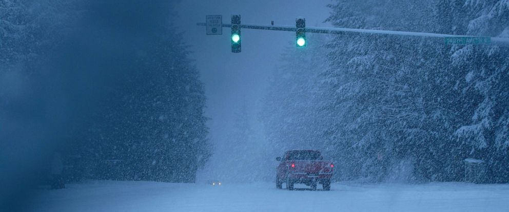 PHOTO: Snow covered intersection with green lights and red truck.