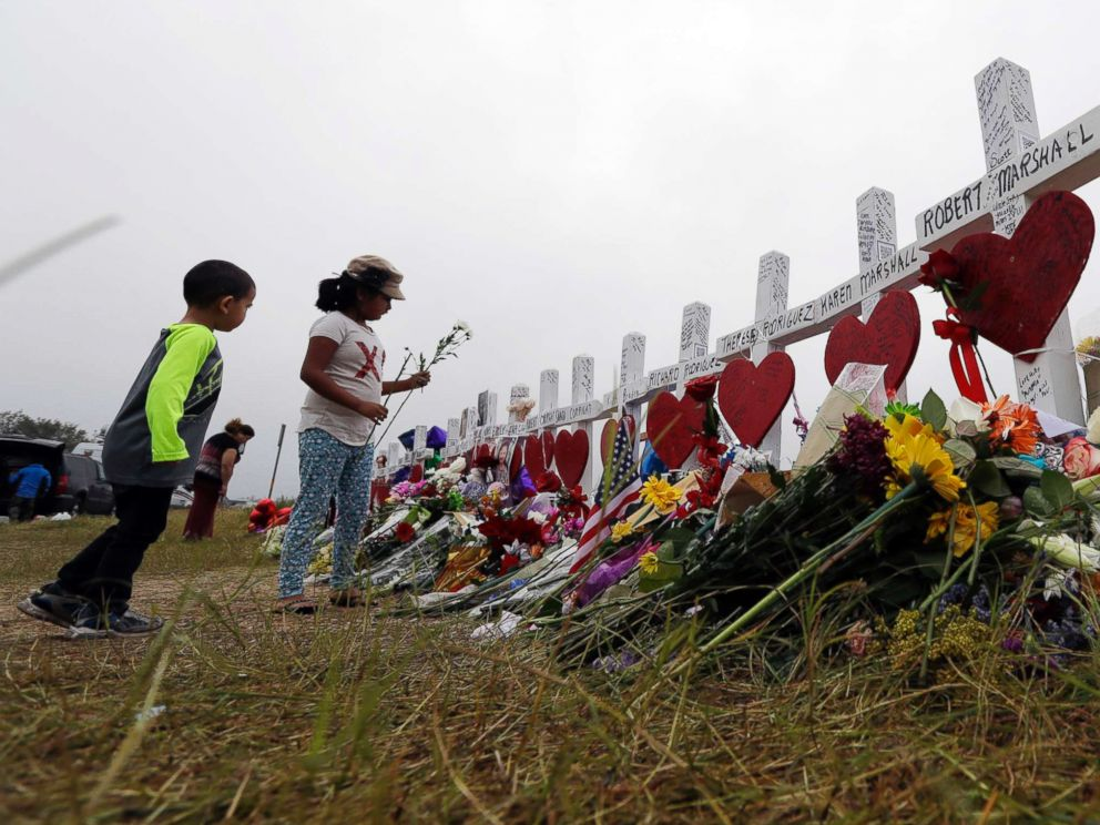 PHOTO: Alexander Osborn and Bella Araiza leave flowers at a makeshift memorial for the victims of the shooting at Sutherland Springs Baptist Church, Nov. 12, 2017, in Sutherland Springs, Texas.