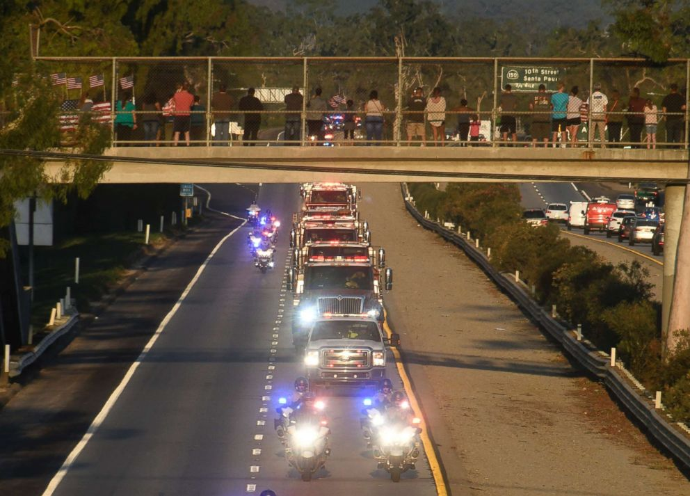 PHOTO: A funeral procession by firefighters and police was organized as people up on the freeway overpasses to pay their respects for firefighter Cory Iverson, Dec. 14, 2017.