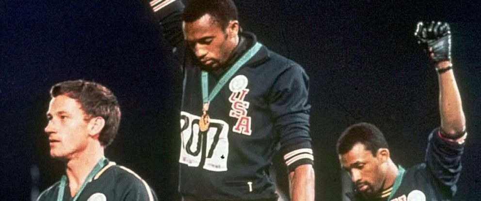 """PHOTO: Athletes Tommie Smith, center, and John Carlos stare downward during the playing of """"The Star-Spangled Banner"""" after Smith received the gold and Carlos the bronze medal in the 200 meter run at the Summer Olympic Games in Mexico City."""