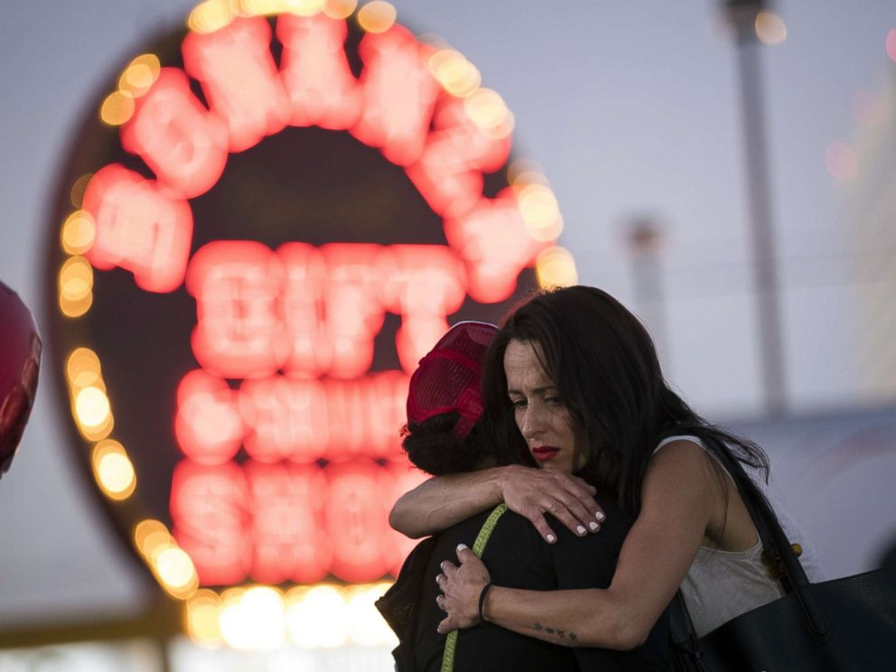 PHOTO: Las Vegas resident Elisabeth Apcar, right, hugs a woman at a makeshift memorial on the Last Vegas Strip, Oct. 4, 2017, three days after a mass shooting.