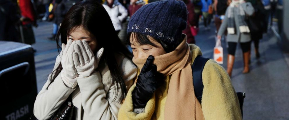 PHOTO: Pedestrians try to keep warm by covering their faces while walking in Times Square, New York, Dec. 27, 2017. Freezing temperatures and below-zero wind chills socked much of the northern United States.