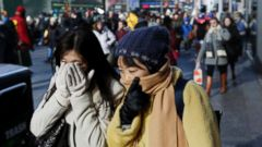 'PHOTO: Pedestrians try to keep warm by covering their faces while walking in Times Square, New York, Dec. 27, 2017. Freezing temperatures and below-zero wind chills socked much of the northern United States.' from the web at 'http://a.abcnews.com/images/US/weather-cold-nyc-times-square-ap-ps-171228_16x9t_240.jpg'