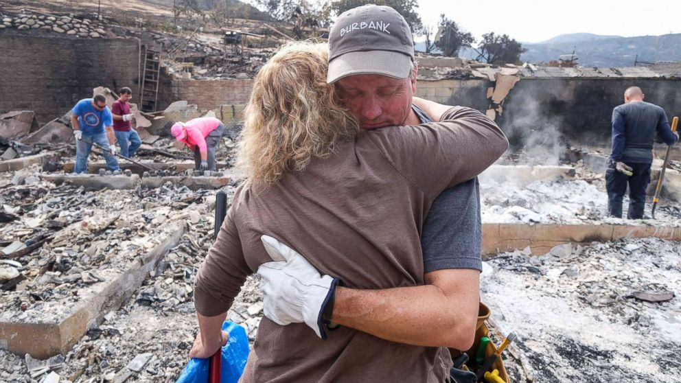 PHOTO: Craig Bolleson hugs his friend in his burned out home, Sept. 4, 2017, in the Sunland-Tujunga section of Los Angeles.
