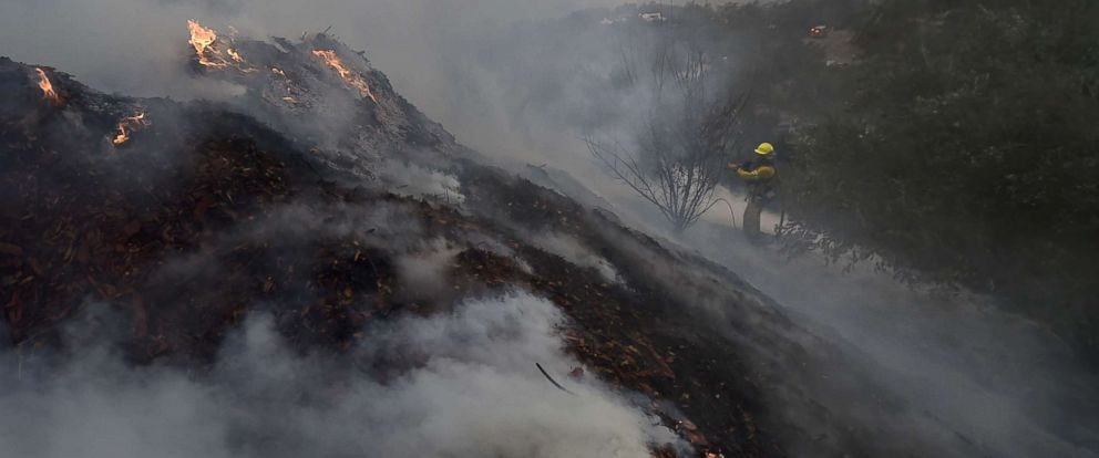 PHOTO: A firefighter puts out hotspots on a smoldering hillside in Montecito, Calif., as strong winds blow smoke and embers inland, Dec. 16, 2017, at the Thomas Fire.