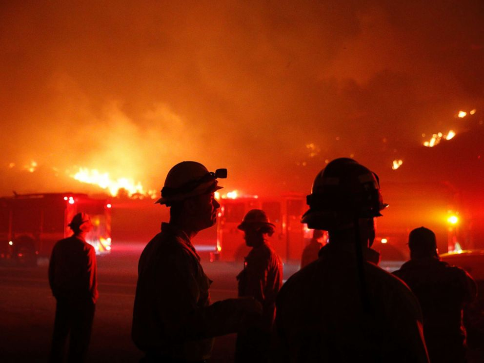 PHOTO: Firefighters gather in front of a residential area as a wildfire burns along the 101 Freeway, Dec. 5, 2017, in Ventura, Calif.