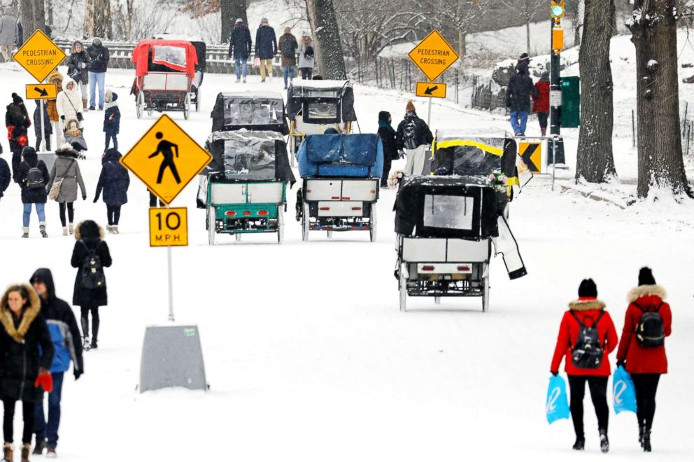 PHOTO: Park-goers and pedi-cabs fill the roadway during a light snow in New Yorks Central Park, Dec. 30, 2017.