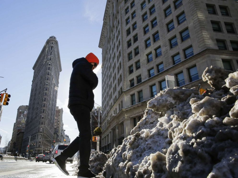 PHOTO: A man walks pass snow accumulated on the sidewalk as the Flatiron Building is pictured during freezing temperatures. Jan. 7, 2018, in New York City.