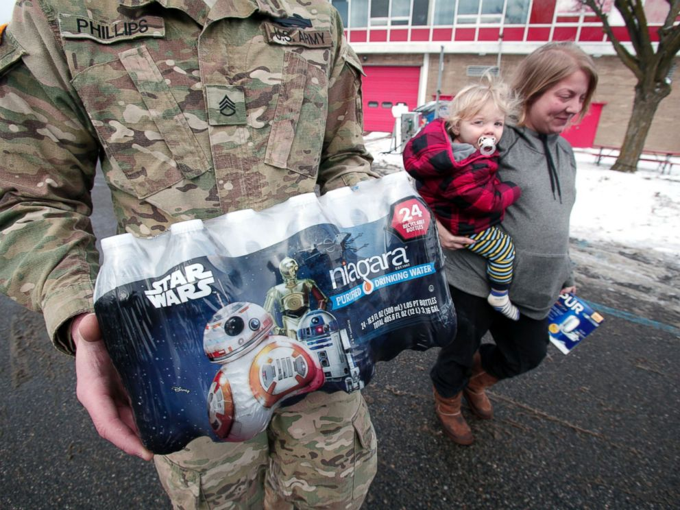 PHOTO:Michigan National Guard Staff Sergeant William Phillips of Birch Run, Mich., helps Flint resident Amanda Roark and her son Dash take bottled water out to her vehicle after she received it at a Flint Fire Station, Jan. 13, 2016, in Flint, Mich.
