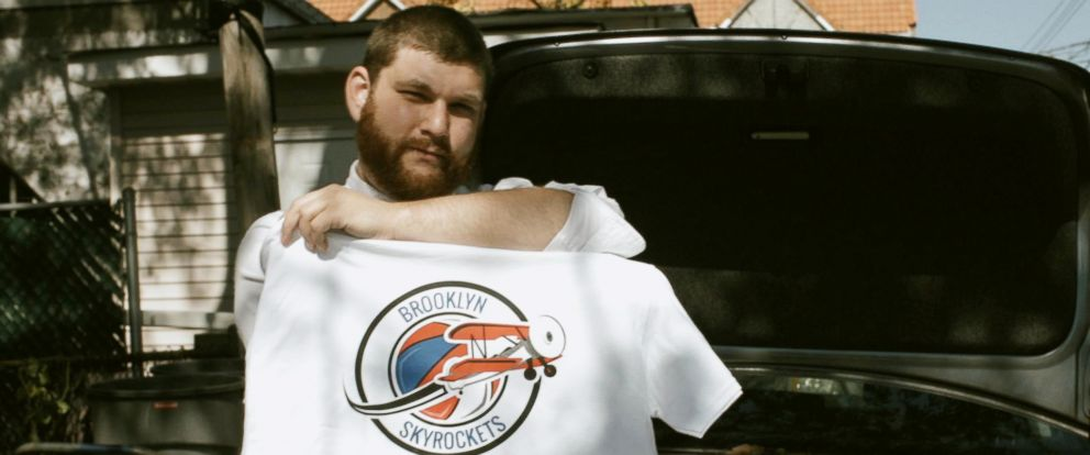PHOTO: Skyrockets owner Dylan Gioia holding his teams t-shirt outside his home in Brooklyn, NY.