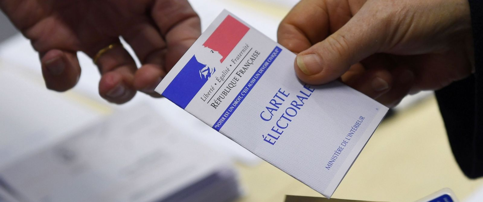 PHOTO: A woman shows her electoral ID before voting at a polling station in Rennes, western France, during the first round of the French presidential election, April 23, 2017.