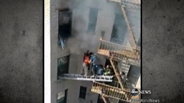 VIDEO: Heroic residents risk their lives hanging from apartment to save neighbor from fire.
