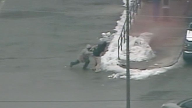 VIDEO: A robber uses a hostage as a human shield, but slips on the ice.