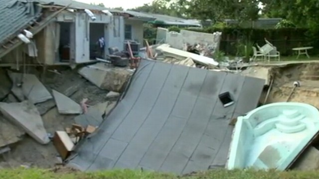 VIDEO: After hearing a rumbling roar at daybreak in Dunedin, Fla., one home collapsed into the earth.