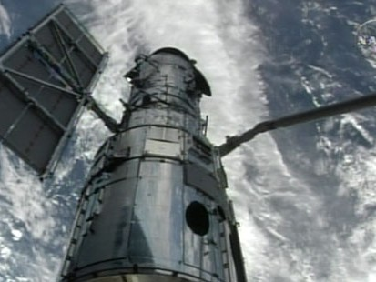 Shuttle crew plucks the telescope out of orbit in a delicate maneuver.