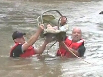 VIDEO: Firefighters helped get the four-week-old infant to higher ground.