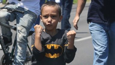 Boy in Batman Shirt Throws His Fists for Muhammad Ali