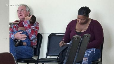 Grandfather cradles stranger's baby in waiting room