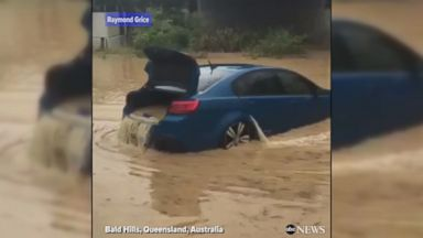 Floodwaters flow through submerged car in Australia