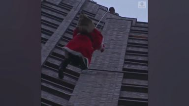 Santa Claus rappels down building to deliver gifts