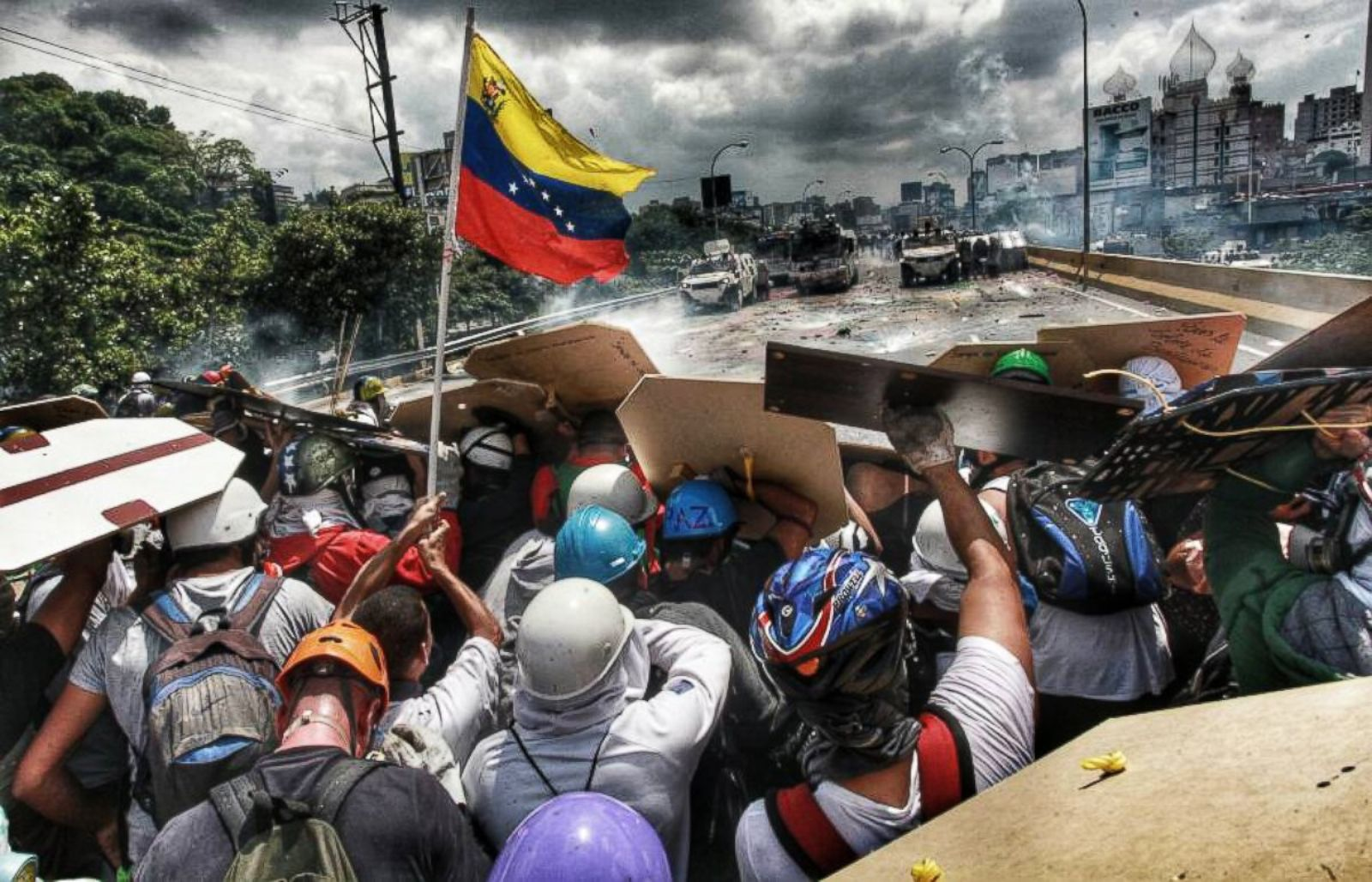 Image result for Young people protect themselves from water sprayed from a tank of the national guard, May 10, 2017, on the Francisco Fajardo motorway in Caracas, Venezuela, during protests against the government.