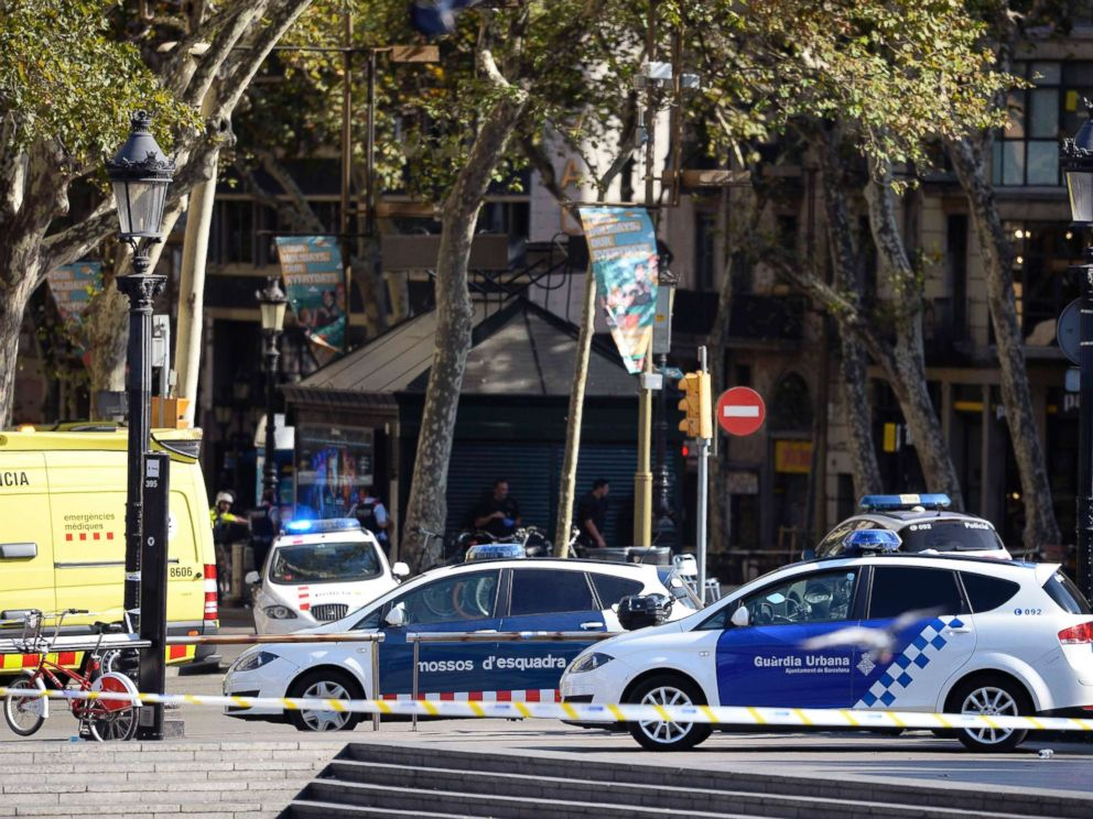 PHOTO: Policemen stand next to vehicles in a cordoned off area after a van ploughed into the crowd, injuring several persons on the Rambla in Barcelona, Aug. 17, 2017.