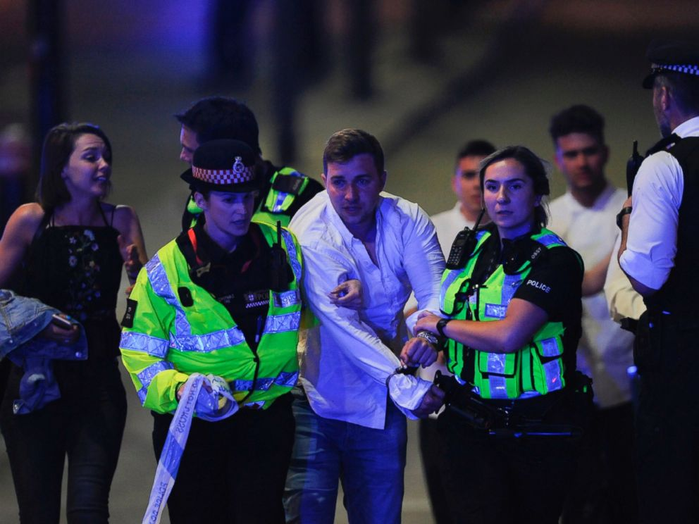 PHOTO: Police escort a member of public as they clear the scene of a terror attack on London Bridge in central London on June 3, 2017.