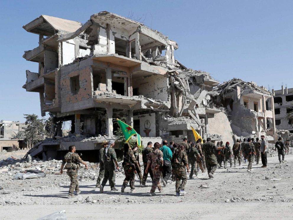 PHOTO: Fighters of Syrian Democratic Forces (SDF) march past destroyed buildings as they celebrate victory and liberation of Raqqa from the Islamic State militants, in Raqqa, Syria, Oct. 17, 2017.