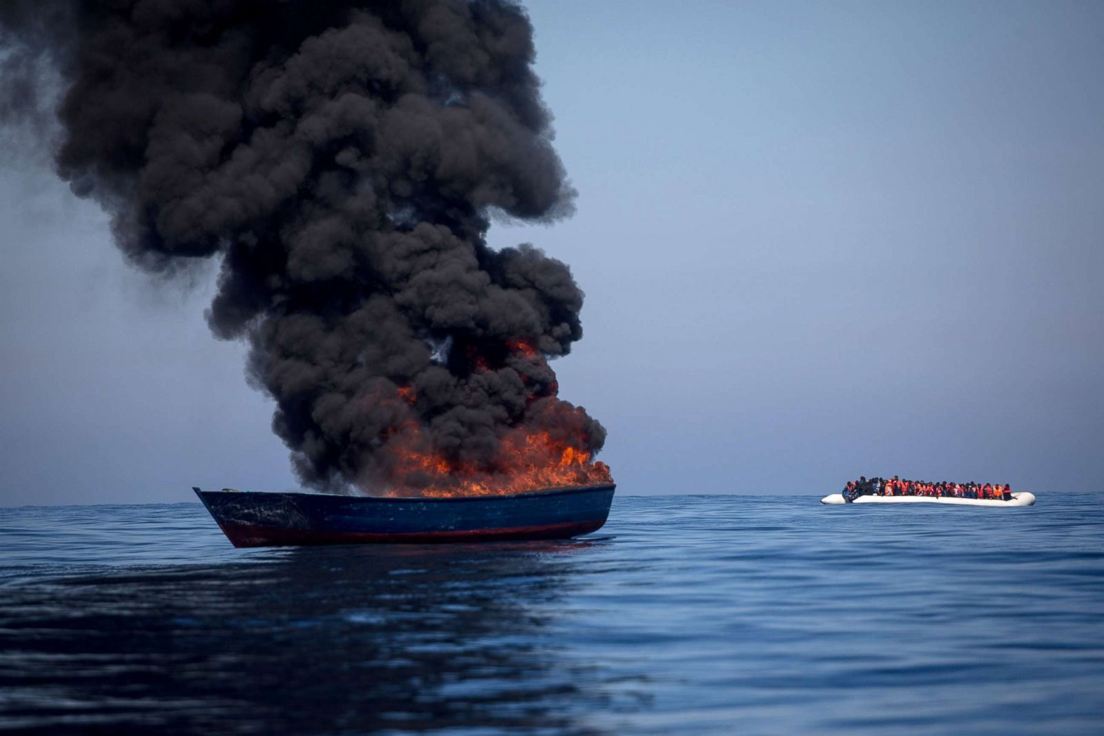 Image result for A small, overcrowded rubber boat filled with migrants passes a boat set alight by rescue crews from the Migrant Offshore Aid Station (MOAS) Phoenix vessel after all passengers were rescued on May 18, 2017 off the coast of Lampedusa, Italy.