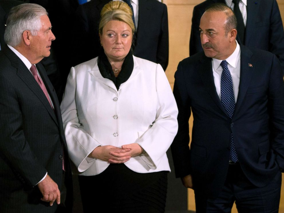 PHOTO: Secretary of State Rex Tillerson, on the left, speaks with the Turkish Foreign Minister Mevlut Cavusoglu, right, during a group photo of the NATO foreign ministers in Brussels, December 5, 2017 British Permanent Representative to NATO Sarah MacIntosh is in the center.