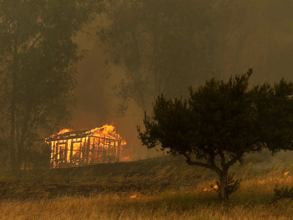 PHOTO: Fire engulfs a structure during a wildfire, May 15, 2014, in Escondido, Calif.