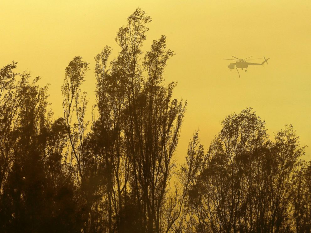 PHOTO: A helicopter transporting water flies over trees, May 15, 2014, in Escondido, Calif.