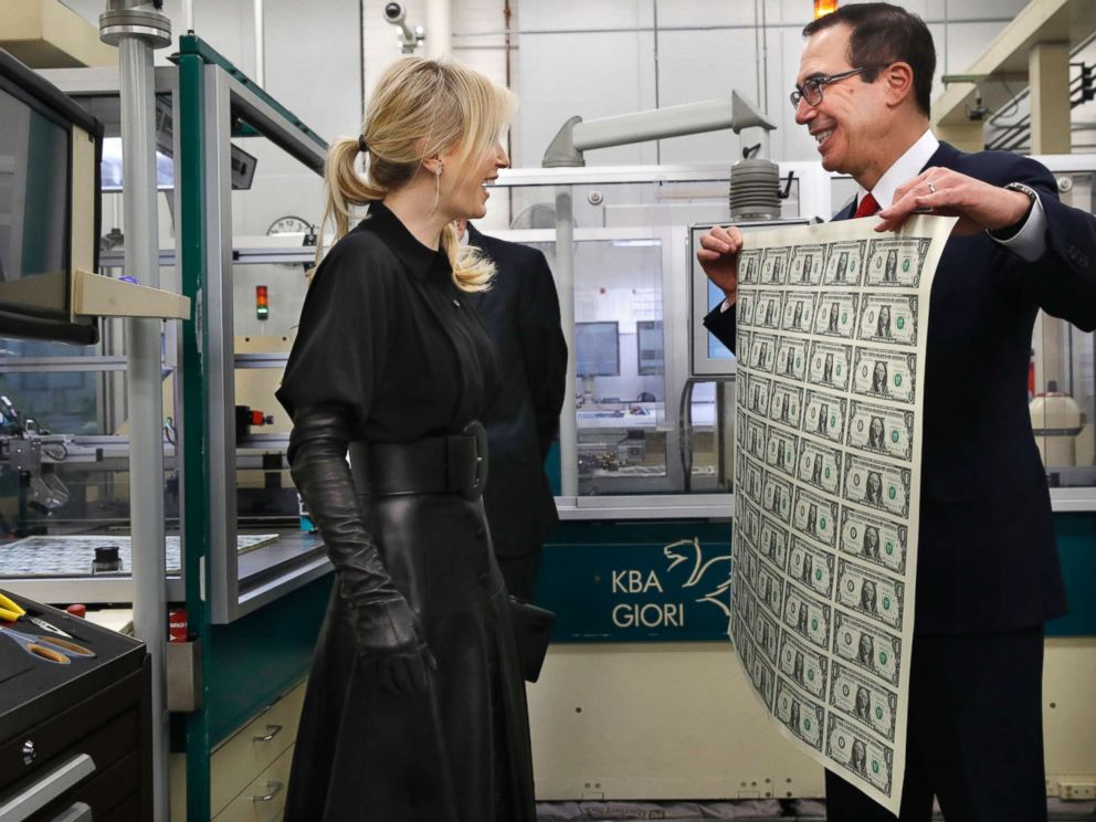 Treasury Secretary Steven Mnuchin, right, and his wife Louise Linton, left, react as Mnuchin holds up a sheet of new $1 bills, the first currency notes bearing his and U.S. Treasurer Jovita Carranzas signatures, Wednesday, Nov. 15, 2017.