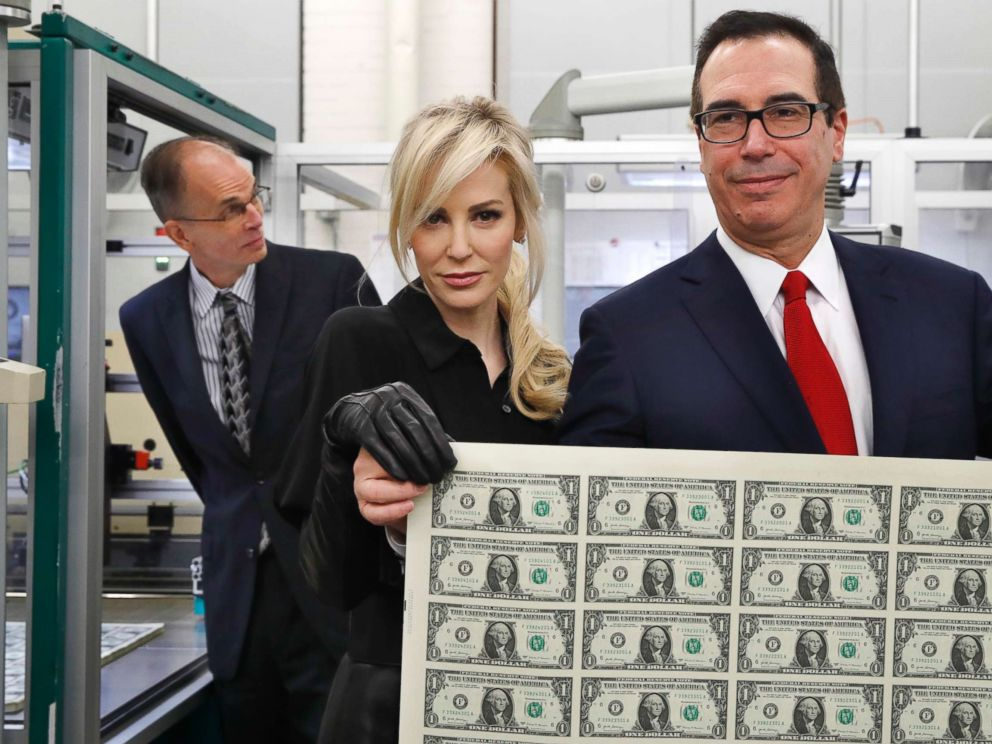 Treasury Secretary Steven Mnuchin, right, and his wife Louise Linton, hold up a sheet of new $1 bills, the first currency notes bearing his and U.S. Treasurer Jovita Carranzas signatures, Wednesday, Nov. 15, 2017.