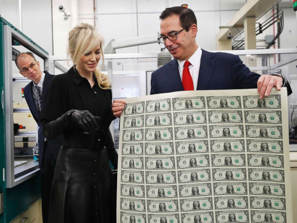 Treasury Secretary Steven Mnuchin, right, shows his wife Louise Linton a sheet of new $1 bills, the first currency notes bearing his and U.S. Treasurer Jovita Carranzas signatures, Wednesday, Nov. 15, 2017.