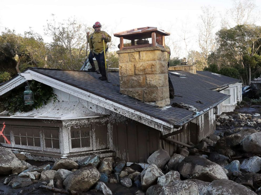 PHOTO: A firefighter stands on the roof of a house submerged in mud and rocks, Jan. 10, 2018, in Montecito, Calif.