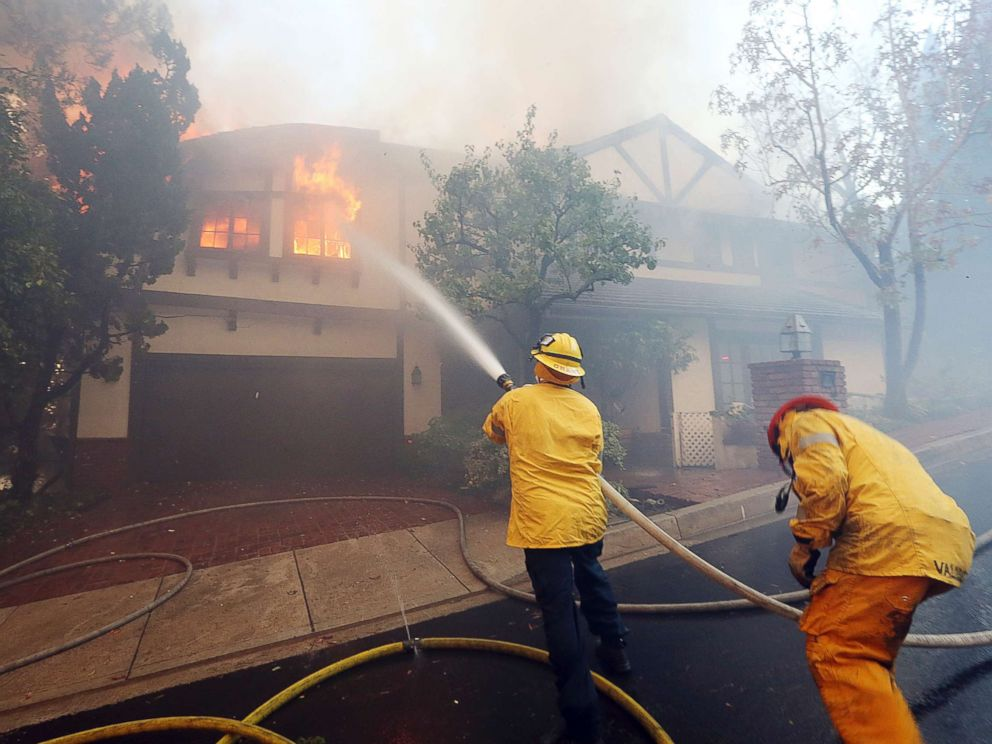 PHOTO: Los Angeles firefighters battle to contain flames to a burning home and prevent the fires spread to adjoining properties in the Bel Air district of Los Angeles on Dec. 6, 2017.