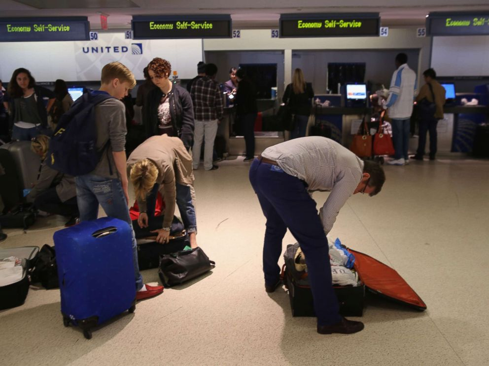 Passengers repack luggage before it is projected onto a new explosives detection system at Newark Liberty International Airport on May 1, 2014.