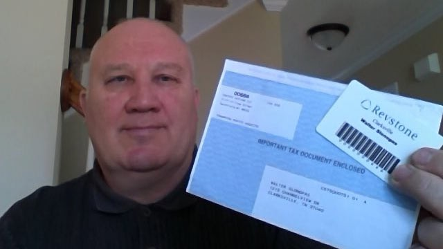 PHOTO: Walter Slonopas holds what he believes are signs of evil- his company identification card and W2 tax form.